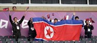 Football fans cheer as the North Korea women's team enters the pitch for their Olympic opener against Colombia in Glasgow on July 25. The London Olympics got off to an embarrassing start when North Korea's women footballers refused to play after a mix-up over their national flag, in one of a series of blunders