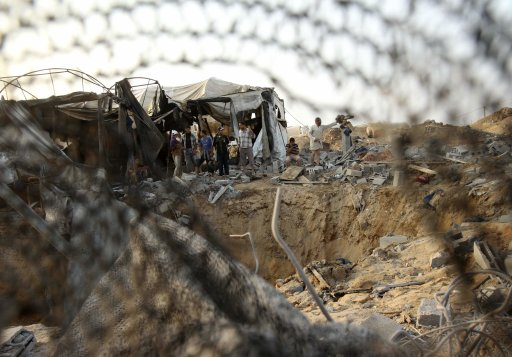 Palestinians survey the damage to a smuggling tunnel after an overnight Israeli air strike in the Gaza Strip
