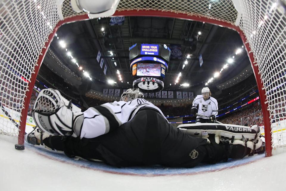 A puck shot by New Jersey Devils' Zach Parise, blocked from view gets past Los Angeles Kings goalie Jonathan Quick (32) during the first period of Game 5 of the NHL hockey Stanley Cup finals Saturday, June 9, 2012, in Newark N.J. (AP Photo/Bruce Bennett, Pool)