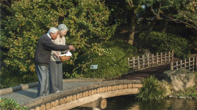 Handout photo shows Japan's Emperor Akihito feeds carp in a pond with Empress Michiko in the garden of the Imperial Residence at the Imperial Palace in Tokyo