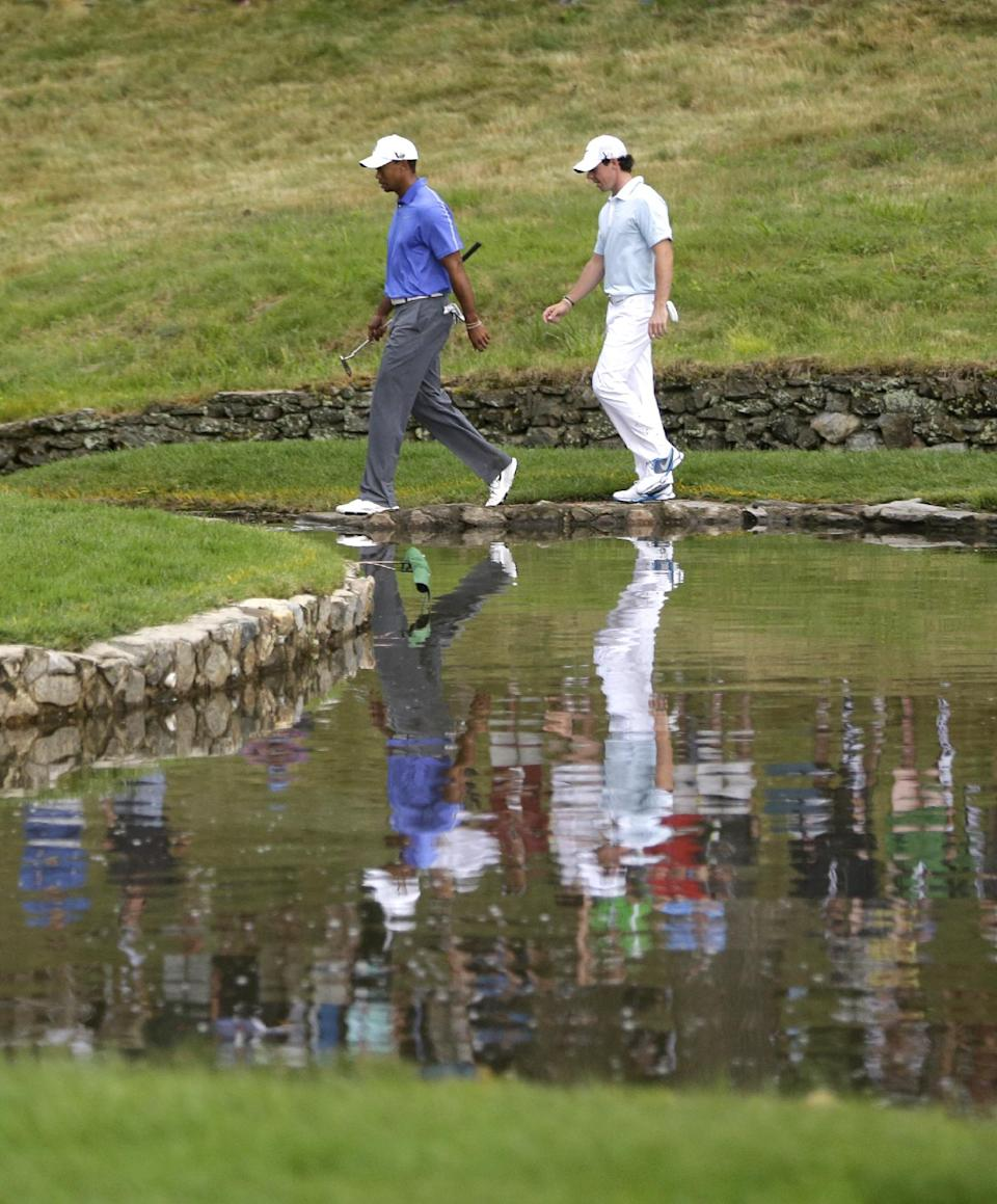 Tiger Woods and Rory McIlroy, of Northern Ireland, walk across a creek on the ninth hole during the first round of the U.S. Open golf tournament at Merion Golf Club, Thursday, June 13, 2013, in Ardmore, Pa. (AP Photo/Gene J. Puskar)