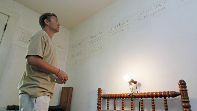 """In this June 8, 2012 photograph, Ryan Spilker, a student at the University of Mississippi, studies the late Nobel Prize laureate William Faulkner's handwriting on the walls of his downstairs office at his antebellum home, Rowan Oak, now a museum owned by the University of Mississippi, in Oxford, Miss. Using pencil, Faulkner outlined events of """"A Fable,"""" a 1954 novel that unfolds during Holy Week and was one of his few books not set in fictional Yoknapatawpha County. Oxford commemorates the 50th anniversary of the Nobel laureate's death July 6 with several events, including a tag-team reading of one of his novels, """"The Reivers,"""" beginning about daybreak. (AP Photo/Rogelio V. Solis)"""