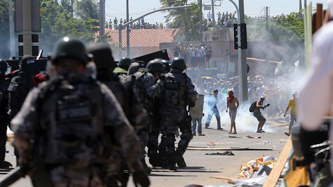Riot police clash with protesters near the Castelao stadium in Fortaleza, Brazil, Wednesday, June 19, 2013. Protesters cut off the main access road to the stadium where Brazil will play Mexico in the Confederations Cup soccer tournament later Wednesday. Beginning as protests against bus fare hikes, the demonstrations have quickly ballooned to include broad middle-class outrage over the failure of governments to provide basic services and ensure public safety. (AP Photo/Andre Penner)