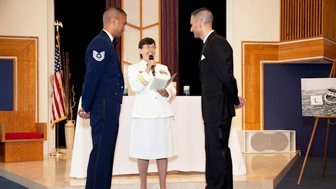 "FILE - In this Saturday, June 23, 2012 photo provided by Jeff Sheng, Navy Chaplain Kay Reeb of the Evangelical Lutheran Church of America officiates the civil union ceremony of Air Force Tech. Sgt. Erwynn Umali, right, and his partner Will Behrens at Joint Base McGuire-Dix-Lakehurst, the military base in Wrightstown, N.J. where Umali is stationed. On Sept. 20, 2011, the repeal of the policy known as ""don't ask, don't tell"" took effect, enabling gay and lesbian members of the military to serve openly, no longer forced to lie and keep their personal lives under wraps. One year later, the Pentagon says repeal has gone smoothly, with no adverse effect on morale, recruitment or readiness. Some critics persist with complaints that repeal has infringed on service members whose religious faiths condemn homosexuality. Instances of anti-gay harassment have not ended. And activists are frustrated that gay and lesbian military families don't yet enjoy the benefits and services extended to other military families. Yet the clear consensus is that repeal has produced far more joy and relief than dismay and indignation. (AP Photo/Jeff Sheng)"