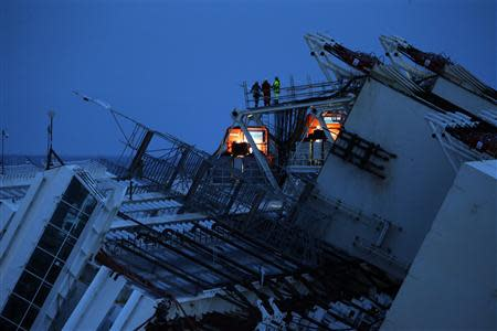 Salvage crew workers are seen on a side of the capsized cruise liner Costa Concordia outside Giglio harbour