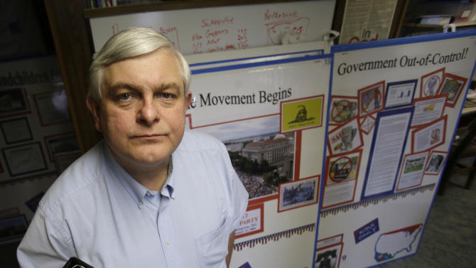 In this May 14, 2013 photo, Tom Zawistowki, founder of the nonprofit Ohio Liberty Coalition, one of the region's largest groups affiliated with the national tea party movement, poses with a binder of documents he gave to the IRS, in Kent, Ohio. For years, Ohio Liberty Coalition would raise thousands of dollars to bus activists to rallies, run phone banks, rent a tent at a local fair, and knock on roughly 40,000 doors across Ohio to challenge the president and his fellow Democrats in the 2012 elections. All the while, the organization was locked in a battle with the nation's tax enforcement agency over whether it should be granted tax-exempt status. (AP Photo/Tony Dejak)