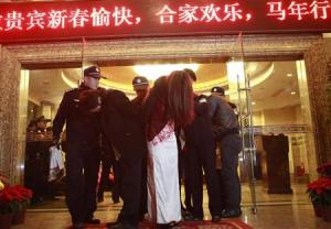 People are taken away during a police action striking prostitution from a hotel in Dongguan