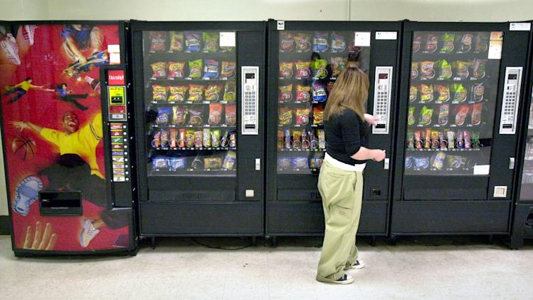 FILE - In this May 3, 2006 file photo, a student purchases a brown sugar Pop-Tart from a vending machine in the hallway outside the school cafeteria, in Wichita, Kan. High-calorie sports drinks and candy bars will be removed from school vending machines and cafeteria lines as soon as next year, replaced with diet drinks, granola bars and other healthier items the Agriculture Department said Thursday, June 27, 2013. (AP Photo/The Wichita Eagle, Mike Hutmacher, File)