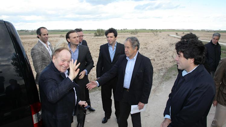 "In this photo released by the Madrid Regional Government on May 6,  2012,  CEO of Las Vegas Sands Corp. Sheldon Adelson, left in foreground, waves while visiting Alcorcon, which was one of the possible sites for the EuroVegas project on the outskirts of Madrid, with others unidentified.  It is announced Sept. 7, 2012, casino giant Las Vegas Sands Corp. has chosen Madrid over Barcelona for a multi-billion dollar gambling resort project dubbed ""EuroVegas"".  With Supporters point out the prospects of construction jobs and service casino jobs will bring improvement to the high jobless rate and shrinking economy in Spain, but critics predict that gambling will attract criminals. (AP Photo/Comunidad de Madrid)"