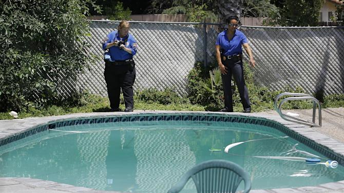 Rialto police detective Carla McCullough, right, and a photographer conduct an investigation at Rodney King's home in Rialto, Calif., Sunday, June 17, 2012. King, the black motorist whose 1991 videotaped beating by Los Angeles police officers was the touchstone for one of the most destructive race riots in U.S. history, died Sunday. He was 47. King's fiancee called police to report that she found him at the bottom of the swimming pool at their home in Rialto, Calif., police Lt. Dean Hardin said. (AP Photo/Jae C. Hong)