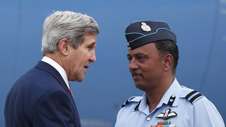 U.S. Secretary of State Kerry arrives as an Indian Air Force officer watches at the airport in New Delhi