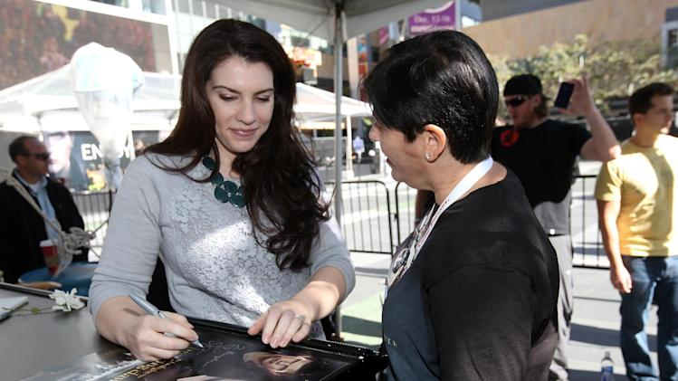 Stephenie Meyer, left, signs autographs for fans at Time Warner Cable's presentation of the Twilight Fan Camp Concert on Saturday, Nov. 10, 2012 in Los Angeles. (Photo by Casey Rodgers/Invision for Time Warner Cable/AP Images)