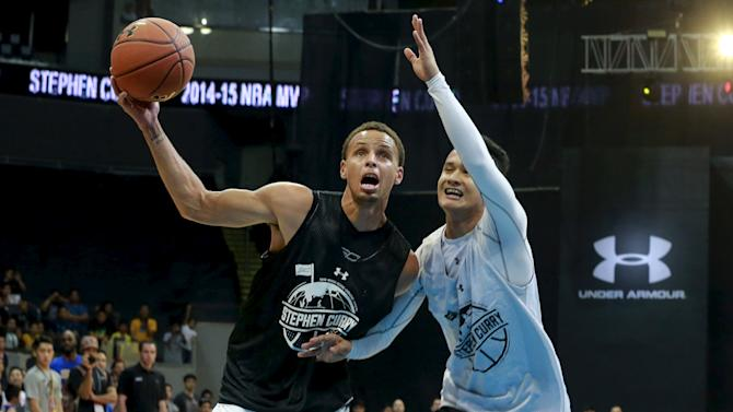 NBA Golden State Warriors' MVP Curry is guarded by a local player during an exhibition game at an arena in Manila