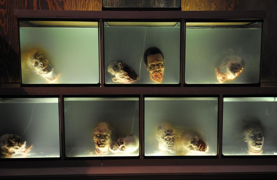 """Walker"" heads float in fish tanks at AMC's ""The Walking Dead"" booth during the Preview Night event on Day 1 of the 2013 Comic-Con International Convention on Wednesday, July 17, 2013 in San Diego. (Photo by Denis Poroy/Invision/AP)"