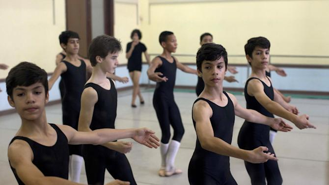 In this April 3, 2013 photo, identical triplets Marcos, left, Cesar, second from right, and Angel Ramirez Castellanos, right, attend their ballet dance class at the National School of Ballet in Havana, Cuba. The Ramirez brothers spend 12 hours a day at the National School of Ballet, housed in a graceful building that occupies a full half-block in colonial Old Havana. Classes include not only dance, but more mundane subjects like language, math and history. (AP Photo/Ramon Espinosa)