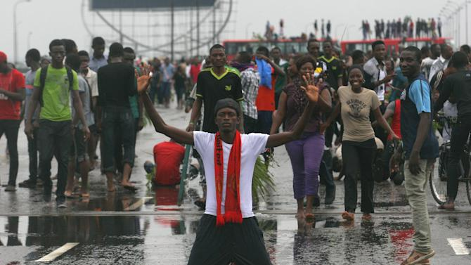 A protestor kneels in the middle of the typically busy Third Mainland Bridge after students blocked traffic in Lagos, Nigeria, Wednesday, May 30, 2012. Students from the University of Lagos and unemployed youths shut down a major bridge in Lagos on Wednesday while protesting a proposed name change for their university.  On Tuesday, President Goodluck Jonathan said the University of Lagos would be renamed Moshood Abiola University in honor of a political prisoner who died in jail over a decade ago. (AP Photo/Jon Gambrell)
