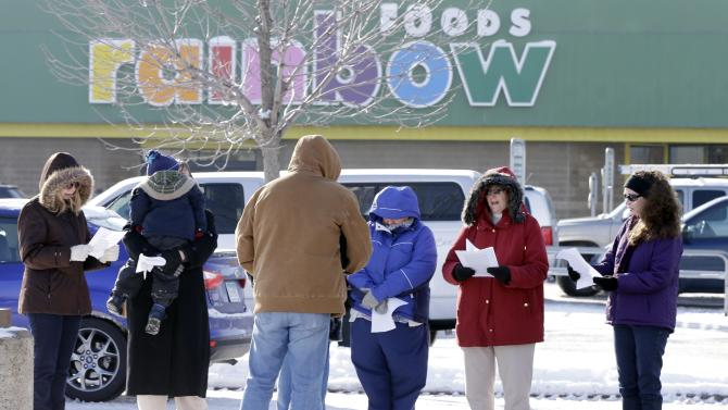 Pastor Chris Duckworth of Grace Lutheran Church of St. Paul, Minn., leads a small group in song outside a Rainbow Foods store Tuesday, Feb. 12, 2013 in Oakdale, Minn., following an apparent random shooting at passing vehicles near the store that left a 9-year-old boy dead and his mother and another woman wounded. The victims in the two vehicles sped to the food store for help.  A 34-year-old Oakdale man is in custody.(AP Photo/Jim Mone)