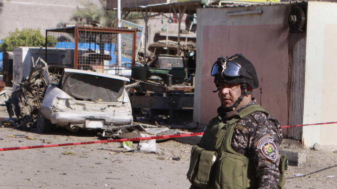 A police man stands guard at the scene of a car bomb attack in the Shiite stronghold of Sadr City, Baghdad, Iraq, Tuesday, March 19, 2013. Insurgents unleashed deadly attacks Tuesday against Shiite areas in Baghdad, killing and wounding scores of people, police said. (AP Photo/ Karim Kadim)