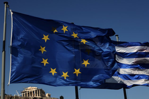 An EU and a Greek flag fly in front of ancient Parthenon temple, in Athens, Sunday, June 17, 2012 as Greeks vote in the most crucial elections in decades. Greece voted Sunday amid global fears that victory by parties that have vowed to cancel the country's international bailout agreements and accompanying austerity measures could undermine the European Union's joint currency and pitch the world's major economies into another sharp downturn. (AP Photo/Petros Giannakouris)