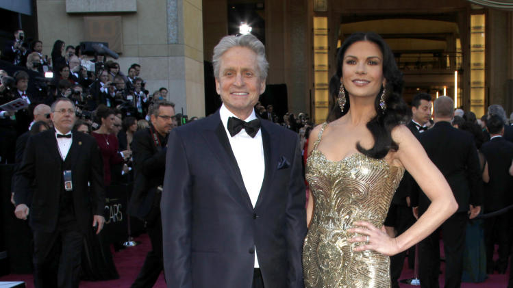 FILE - In this Feb. 24, 2013 file photo, actors Michael Douglas, left, and Catherine Zeta-Jones arrive at the Oscars at the Dolby Theatre, in Los Angeles. According to her publicist on Monday, April 29, 2013, Zeta-Jones has pro-actively checked into a health care facility. Previously, she has said that she is committed to periodic care in order to manage her health in an optimum manner. (Photo by Carlo Allegri/Invision/AP, File)