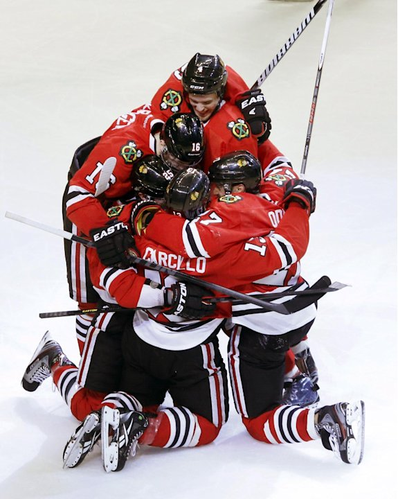 Chicago Blackhawks left wing Daniel Carcillo, bottom center, is mobbed by teammates as they celebrate Carcillo's winning goal during the third period of an NHL hockey game against the Colorado Avalanc