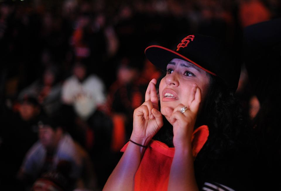 San Francisco Giants fan Brianna Cuadra watches a broadcast on a television outside San Francisco's City Hall as the Giants face the Detroit Tigers to win in Game 4 of baseball's World Series on Sunday, Oct. 28, 2012. (AP Photo/Noah Berger)