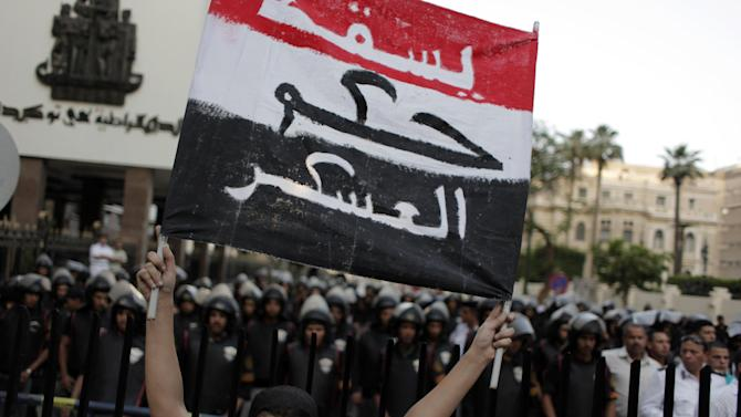 """A protester holds a placard in the colors of the Egyptian flag and Arabic that reads, """"down with the military rule,"""" in front of riot police during a rally demanding the release of fellow activists, detained during the army operation that dispersed a protest in front of the Ministry of Defense, in Cairo, Egypt, Sunday, May 6, 2012. (AP Photo/Nasser Nasser)"""