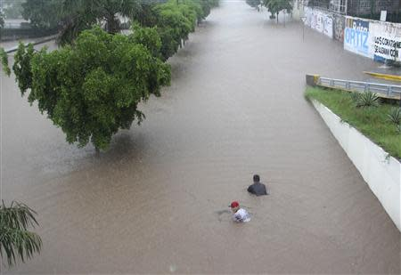 People swim in floodwaters in Culiacan