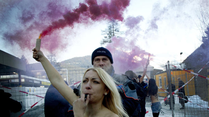 """Swiss police arrest  activists of the Women's Movement """"FEMEN"""" outside the congress centrum at the 43rd Annual Meeting of the World Economic Forum, WEF, in Davos, Switzerland, Saturday, Jan. 26, 2013.  (AP Photo/Anja Niedringhaus)"""