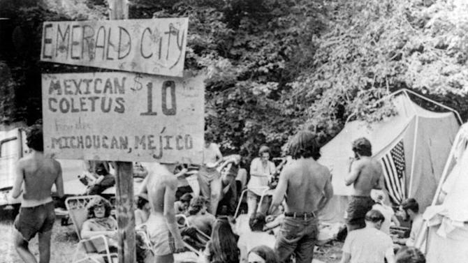"FILE - In this Aug. 1, 1970, file photo, youths sell marijuana openly from sacks at a banned music festival in Middlefield, Conn. beneath a sign advertising their products as ""Mexican Coletus at $10 an ounce.""As the conformity of the postwar era took hold, getting high on marijuana and other drugs emerged as a symbol of the counterculture, with Jack Kerouac and the rest of the Beat Generation singing pot's praises. On the occasion of  ""Legalization Day,"" Thursday, Dec. 6, 2012, when Washington's new law takes effect, AP takes a look back at the cultural and legal status of the ""evil weed"" in American history. (AP Photo/File)"