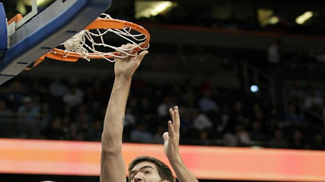 Charlotte Bobcats' Byron Mullens (22) dunks the ball as he gets between Orlando Magic's Glen Davis (11) and Ryan Anderson (33) during the first half of an NBA basketball game, Wednesday, April 25, 2012, in Orlando, Fla. (AP Photo/John Raoux)