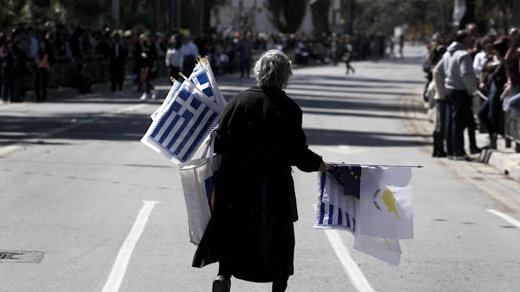 """An elderly woman sells Greek, Cypriot, and EU flags before the start of a parade for Greek Independence Day celebrations in capital Nicosia, Cyprus, Monday, March 25, 2013. Cyprus secured what its politicians described as a """"painful"""" solution to avert imminent bankruptcy, agreeing early Monday to slash its oversize banking sector and make large account holders take losses to help pay to secure a last-minute euro10 billion (US$13 billion) bailout. (AP Photo/Petros Giannakouris)"""