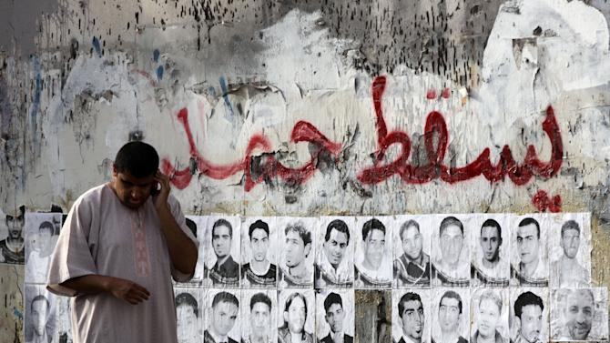 """A Bahraini man talks on his phone as he walks past pictures of prisoners held in connection with the pro-democracy uprising in the Gulf nation Sunday, May 27, 2012, in the western village of Karzakan, Bahrain. The Arabic writing on the wall reads, """"down Hamad,"""" referring to the Bahraini king. A Bahrain court sentenced eight people to prison terms of up to 15 years Sunday after they were accused of plotting with suspected Iranian agents to topple the Gulf kingdom's ruling system, a defense lawyer said. (AP Photo/Hasan Jamali)"""
