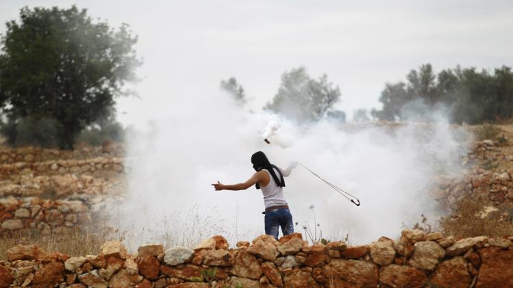A stone-throwing Palestinian protester uses a sling to throw back a tear gas canister fired by Israeli soldiers during clashes near Ramallah