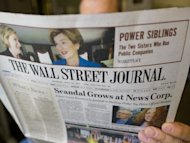 This file photo shows a person reading The Wall Street Journal, in July 2011 in Washington,DC. The board of Rupert Murdoch's News Corp has agreed in principle to separate its larger entertainment division from struggling publishing businesses, according to the paper