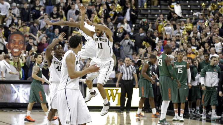 Wake Forest players celebrate as Miami players walk off the court after an NCAA college basketball game in Winston-Salem, N.C., Saturday, Feb. 23, 2013. Wake Forest won 80-65. (AP Photo/Chuck Burton)