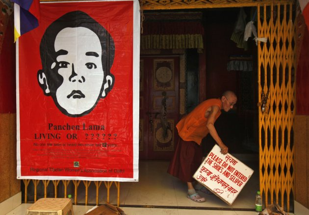 A Tibetan monk holds a sign board next to a poster of Gedhun Choekyi Nyima at a monastery after a sit-in protest against the visit of Chinese Premier Li at Majnu Ka Tila in New Delhi