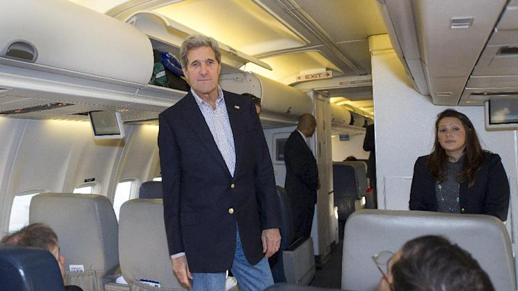U.S. Secretary of State John Kerry talks to reporters traveling abroad with him shortly after finding out their aircraft had a mechanical problem before take off Saturday, April 6, 2013, at Andrews Air Force Base in Maryland. A backup aircraft was brought in to replace the plane. (AP Photo/Paul J. Richards, Pool)