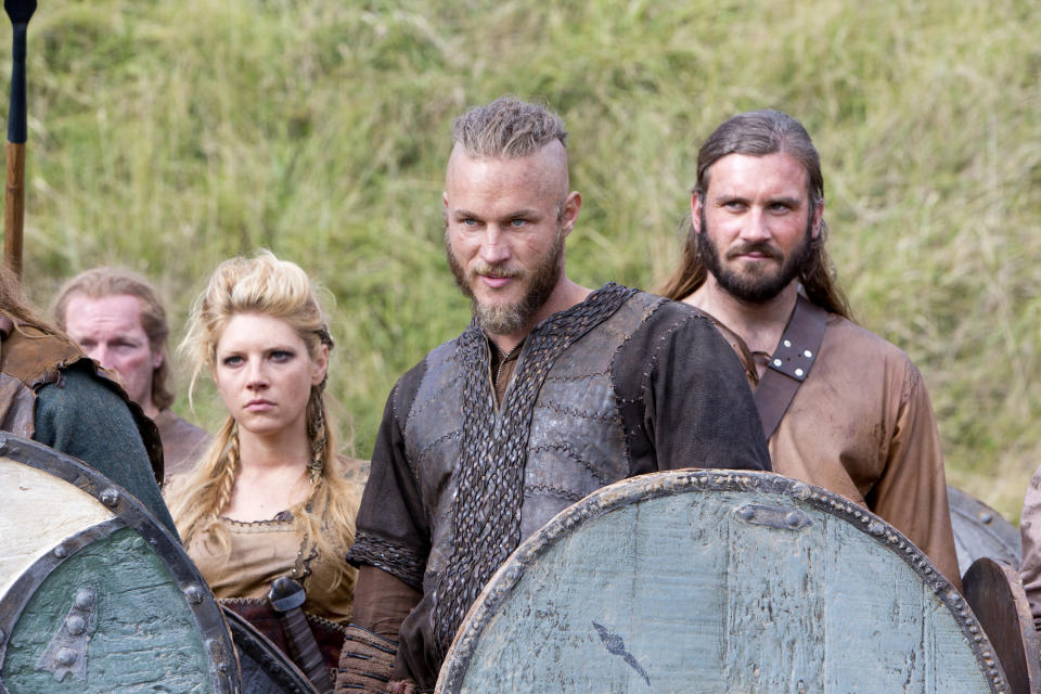 "This image released by History shows Katheryn Winnick, as Lagertha, left, Travis Fimmel, as Ragnar, center, and Clive Standen as Rollo in a scene from ""Vikings,"" premiering Sunday, March 3 on History. (AP Photo/History, Jonathan Hession)"