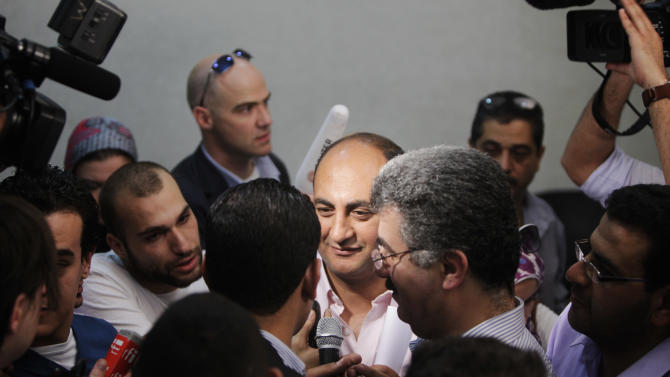 Presidential candidate Khaled Ali is surrounded by journalists following a presser on the interim constitution, which is expected to be released in a few days, at his campaign headquarters in Cairo, Egypt, Monday, May 21, 2012. The May 23-24 presidential election is the first since last year's ouster of longtime authoritarian ruler Hosni Mubarak. It marks the first time Egyptians will choose their leader in a race overseen by international monitors. (AP Photo/Amr Nabil)