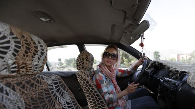 Kanaz listens to her instructor during a practical driving test in Kabul