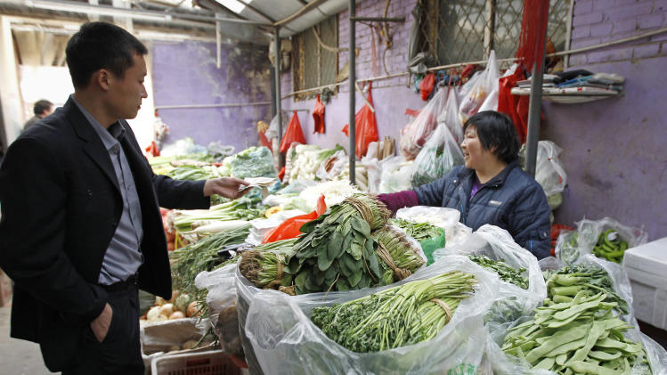 A customer buys vegetable at a market in Beijing Friday, March 11, 2011. China's February inflation held steady at 4.9 percent, the National Bureau of Statistics announced Friday, March 11, 2011 as the rise in food prices accelerated, adding to pressure for the communist government to control surging living costs that it worries could fuel unrest. (AP Photo/Vincent Thian)
