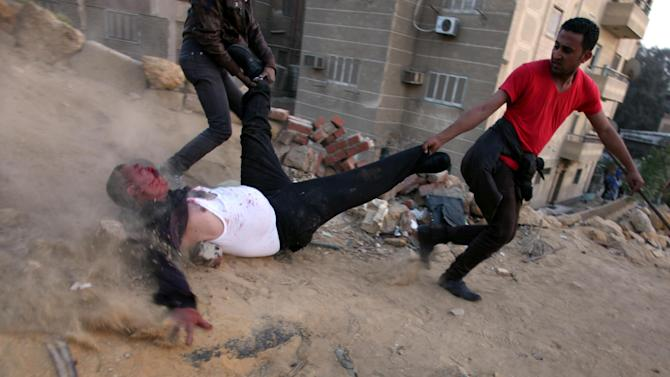 AP10ThingsToSee - Egyptian protesters drag a wounded Muslim Brotherhood supporter during clashes between supporters and opponents of Egypt's powerful Muslim Brotherhood near the Islamist group's headquarters in Cairo, Egypt, Friday, March 22, 2013. (AP Photo/Khalil Hamra, File)