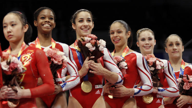 USA'S gymnasts from second left, Gabrielle Douglas, Alexandra Raisman, Sabrina Vega, McKayla Maroney and Jordyn Wieber, celebrate on the podium after winning the women's team final at  the Artistic Gymnastics World Championships in Tokyo, Japan, Tuesday, Oct. 11, 2011. (AP Photo/Bullit Marquez)
