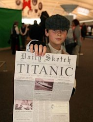 This handout photo released by the Titanic Memorial Cruises shows a child posing with a memorial newspaper in the departure lounge of the MS Balmoral cruise ship in Southampton on April 8. Passengers then plan to throw wreaths into the sea at 2:20 am about 800 kilometers (500 miles) southeast of Halifax at the time and place the ship sank