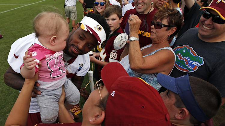 Washington Redskins receiver Santana Moss holds a little fan for a picture after practice at the team's NFL football training facility, Sunday, July 27, 2014, in Richmond, Va