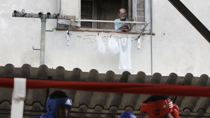 In this March 9, 2013 photo, a man peers from his home's window to watch boxer Frank Sanchez, left, fight with Julio Bernal during a boxing tournament at the Rafael Trejos boxing gym in Old Havana, Cuba. In 1961, two years after the Cuban Revolution, all professional sports were banned and the very concept has been anathema to the island government's Marxist ideals ever since. Now the island is on the verge of partially reversing five decades of strictly amateur boxing. (AP Photo/Franklin Reyes)
