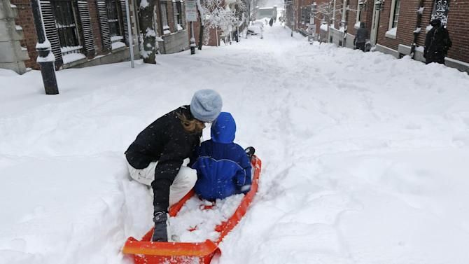 A woman prepares to launch her child down a snow-covered street in the Beacon Hill neighborhood of Boston, Saturday, Feb. 9, 2013. The Boston area received about two feet of snow from a winter storm. A howling storm across the Northeast left the New York-to-Boston corridor shrouded in 1 to 3 feet of snow Saturday, stranding motorists on highways overnight and piling up drifts so high that some homeowners couldn't get their doors open. More than 650,000 homes and businesses were left without electricity. (AP Photo/Charles Krupa)