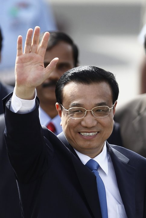 Chinese Premier Li waves upon his arrival at the airport in New Delhi