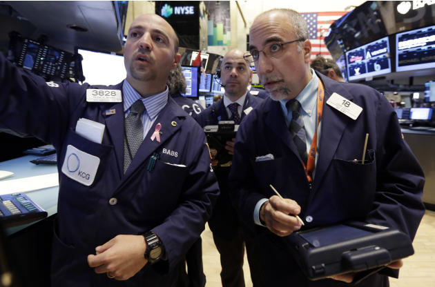 Specialist Frank Babino, left, works with traders Fred DeMarco, center, and John Liotti on the floor of the New York Stock Exchange Wednesday, March 12, 2014. U.S. stocks are heading lower for the thi